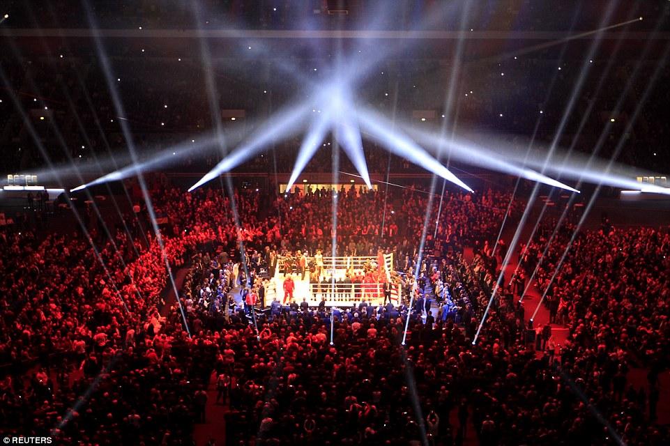 Через несколько минут два тяжеловеса сойдутся на ринге, подобно лучам лазера под потолком спортивной арены в Германии.
